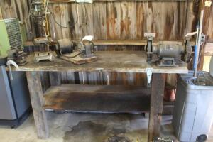Wooden work bench with vise and grinder attached.