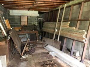 Contents of garage bay, includes metal trailer frame, scrap metal, lumber and more
