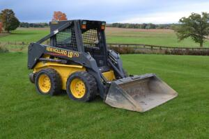 New Holland LS 170 Skid loader with material bucket and double tine hay spear attachment